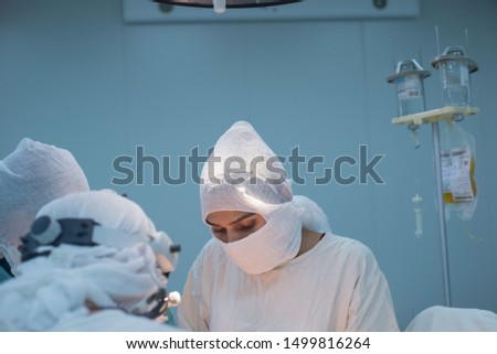 operational team. Girl surgeon looking at the camera during an operation. Conditions for a sterile operating room. Surgical intervention