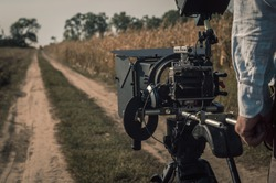 Operator filming with compact mirrorless camera rig outdoors. Filmmaking scene