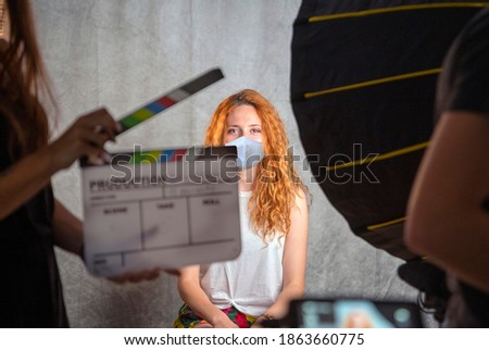 Operator holding clapperboard during the production of short film. Actress with red hair and surgical mask on stage. Blur effect on the clapperboard and monitors. work in times of Coronavis, Covid-19. Stock fotó ©