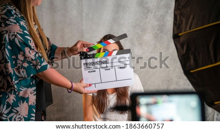 Operator holding clapperboard during the production of short film inside a studio with young actress on stage. Focus on the clapperboard and blur effect on the monitor and model. Stock fotó ©