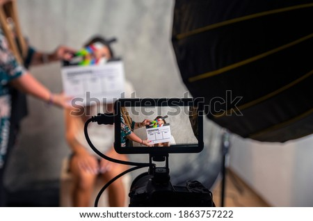 Operator holding clapperboard during the production of short film inside a studio with young actress on stage. Blur effect on the clapperboard and focus on monitor.