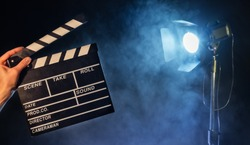 Operator holding clapperboard, studio light with claps on background. Filmmaker background