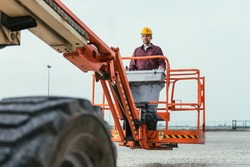 Operator In Safety Helmet and red square shirt controlling Straight Boom Lift