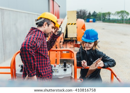 Operator In Safety Helmet and red square shirt receiving instruction for Straight Boom Lift