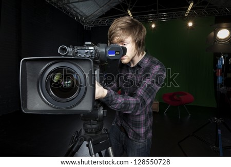 Operator looks into the viewfinder of a television studio camera, with lights and CSO green curtain in the background.