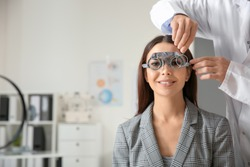 Ophthalmologist examining young woman in clinic