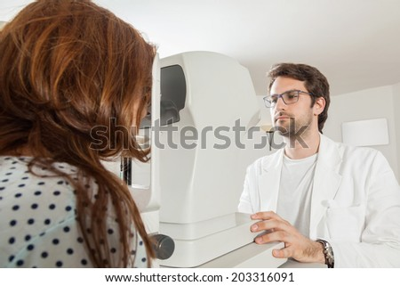 Ophthalmologist In Exam Room With Young Woman Sitting In Chair Looking Into Eye Test Machine
