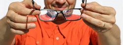 ophthalmologist optician lets the myopic patient try glasses in th shop