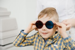 Ophthalmologist tests child kid boy for color blindness, eye vision test.