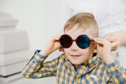 Ophthalmologist tests child kid boy for color blindness, eye vision test.