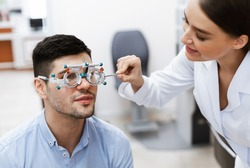 Ophthalmology Concept. Portrait of cheerful female specialist examining guy with modern equipment, using trial frame. Optometrist ophthalmologist doctor testing patient with diagnostic tool