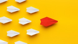 Opinion leadership. Red paper plane leading another colorful ones, influencing the crowd, yellow background, panorama