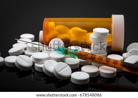 Opioid epidemic and drug abuse concept with a heroin syringe or other narcotic substances next to a bottle of prescription opioids. Oxycodone is the generic name for a range of opioid painkillers #678548086
