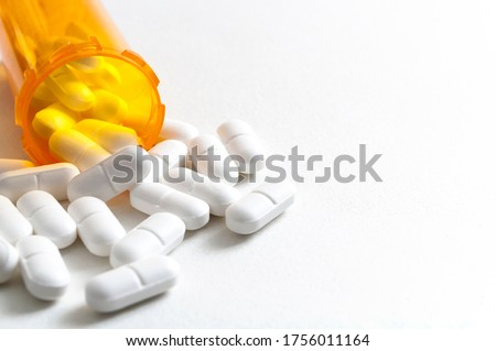 Opioid epidemic, drug abuse and overdose concept with scattered prescription opioids spilling from orange bottle with copy space. Hydrocodone is the generic name for a range of opiate painkillers Сток-фото ©