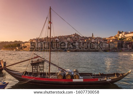 Oporto, Portugal - Douro river with traditional boats and city skyline with colorful houses at summer sunset