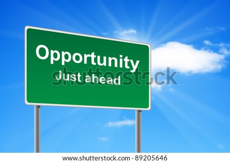Opportunity road sign on background clouds and sunburst. - stock photo