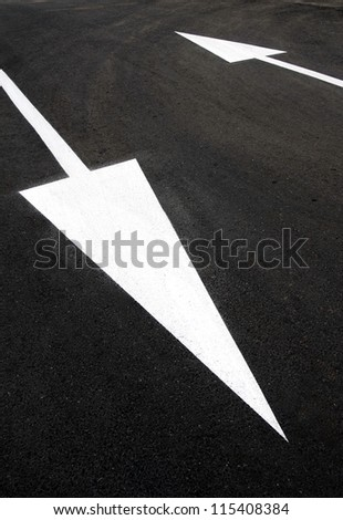 Opposite directions: two up and down white arrows on black asphalt ...