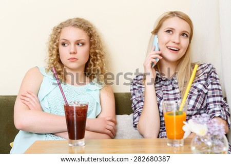 Stock Photo Opposite feelings. One girl talking per phone and another sitting with crossed arms in cafe.