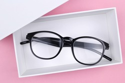 Optical glasses in a stylish black frame are in a white gift box on a pink background.The concept of discounts,promotions, sales in optics stores, repair of glasses,glasses as a gift.Copyspace