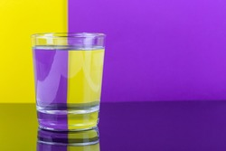 Optical illusion with glass of water and colorful paper, yellow and violet background, horizontal,  copy space