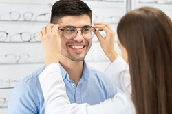 Optical Shop. Female optician in white coat helping handsome guy to buy eyeglasses, selective focus