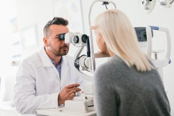 Optician checking his patient's eyes. Medical examination, proffesional optic machine.