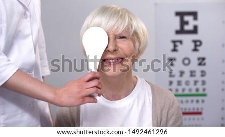 Optician closing elderly ladies eye, maintaining satisfactory eyesight, test