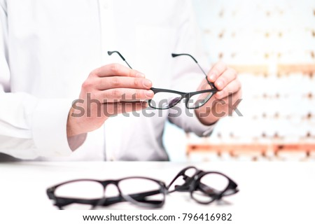 Optician in store holding glasses. Eye doctor with lenses. Professional optometrist in white coat with many eyeglasses. Shop interior. Fixing or comparing different options in spectacles.