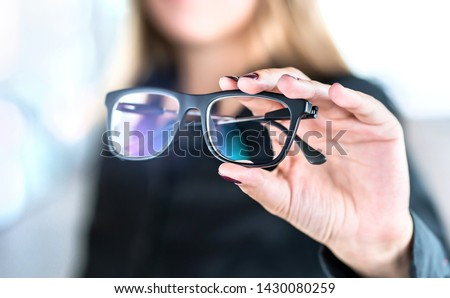 Optician, optometrist, oculist or eye doctor holding glasses and specs with new lenses. Professional eyesight specialist in clinic or shop with spectacles in hand. Bifocal or multifocal eyeglasses.