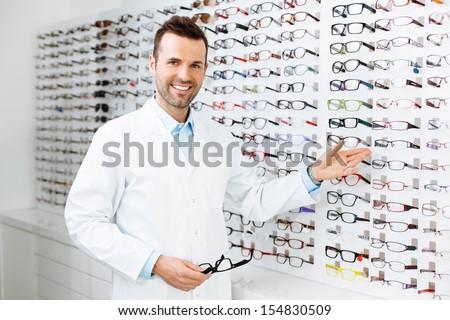 Optician selling glasses. Eye doctor, optometris at work.