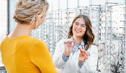 Optician suggesting and showing eyeglasses in an optical shop, finding the right frame for prescription glasses
