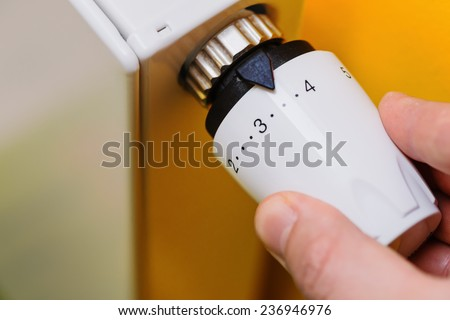 Optimal setting of the thermostat valve. Radiator adjustment to save energy. Save energy and money concept