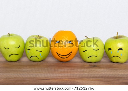 Optimist between pessimists and good mood concept, apples with drawn sad faces and an orange with a smile.