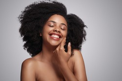 Optimistic African American woman with curly hair smiling with closed eyes and touching perfect skin of cheek against gray background