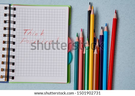 Optimistic Attitude and Happy Concept. Colored pencils and the words think positive in notepad
