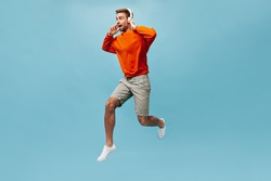 Optimistic brown haired man with beard in sweatshirt, shorts and sneakers holding white headphones and jumping on isolated background..