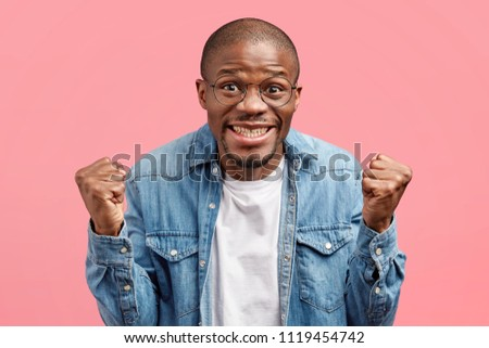 Optimistic dark skinned male keeps fists clenched, celebrates his successful deal in business sphere, dressed in denim jacket, poses over pink background. People, happiness and triumph concept