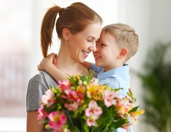 Optimistic family: mother with bouquet of  alstroemeria laughing and touching nose with happy son  during holiday celebration  mothers day at home