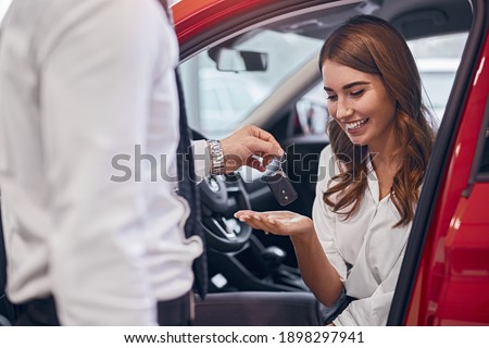 Optimistic female client sitting in brand new car and taking keys from crop dealer in dealership
