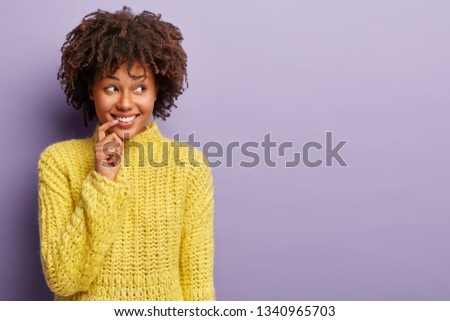 Optimistic glad woman keeps hand near broad smile, shows white teeth, focused aside, dreams about new desirable thing, wears yellow knitted jumper, models over purple background. Emotions concept #1340965703