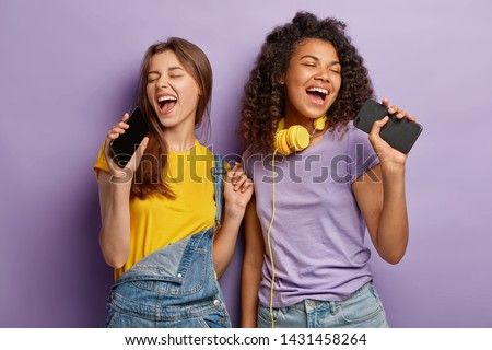 Optimistic pleased mixed race women sing favourite song in smart phones, have fun and enjoy music, keep eyes shut, move actively, isolated on purple background. People, free time and joy concept