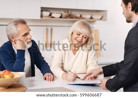 Optimistic senior couple signing documents at home - Shutterstock ID 599606687
