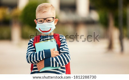 Optimistic smart first grade schoolboy in casual wear and eyeglasses wearing protective mask with drawn smile holding copybooks and looking at camera against blurred urban background Foto stock ©
