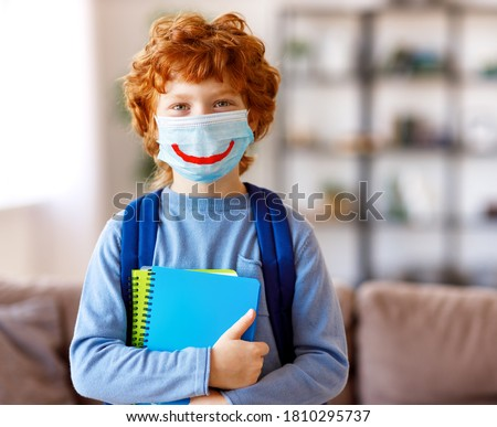 Optimistic smart ginger schoolboy in casual wear  wearing protective mask with drawn smile holding copybooks and looking at camera   at home Foto stock ©