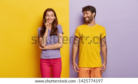Optimistic young female and male with broad smiles, feel happy, dressed in casual clothes, have fun together, stand against purple and yellow background. People, relations, togetherness concept