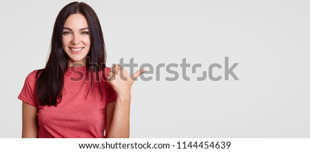 Optimistic young female with toothy friendly smile points aside with thumb, shows blank space for your advertising content or promotional text, has long dark hair, isolated over white background