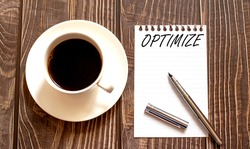 OPTIMIZE - white paper with pen and coffee on wooden background. Business