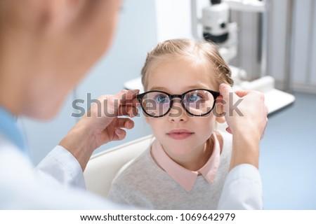 optometrist and little kid in glasses in optics