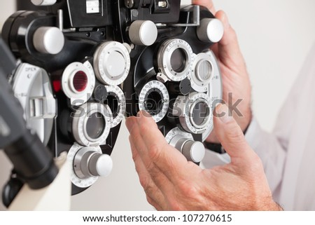 Optometrist changing settings in phoropter before an eye test
