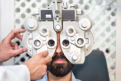 Optometrist doing sight testing for male patient In clinic. Male ophthalmologist examining patient man with optometrist trial frame .